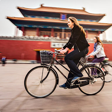 two travelling partners riding their bicycles past an Asian temple.