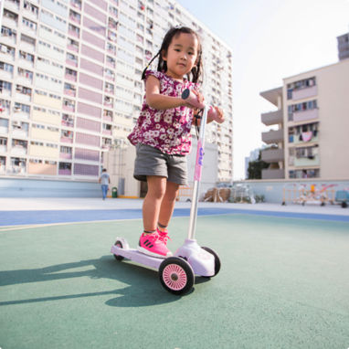 A young girl riding around on her pink, three wheeled scooter.
