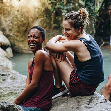 Two young women laughing with each other, sitting by a lake.