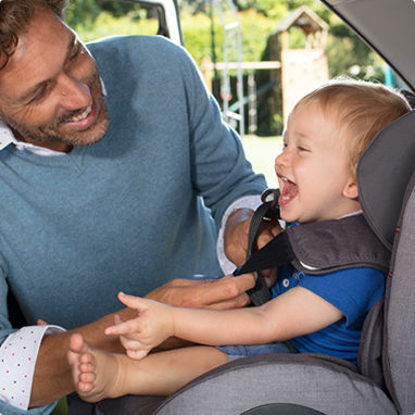 A father buckling his young son in to a toddlers car seat.
