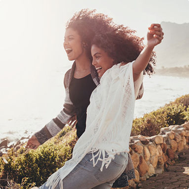 Two young women laughing and embracing in front of a sunny coastal scene.
