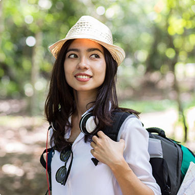 A young woman traveler walking outdoors with her backpack and straw hat.