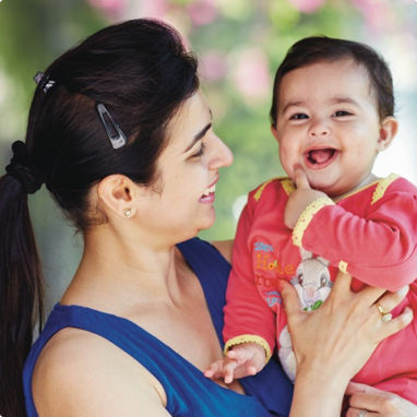 A mother looking at her happy, laughing baby which she is holding.