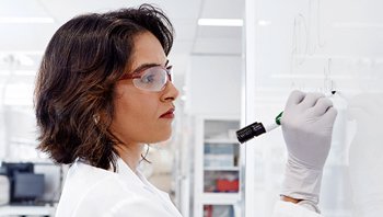 A female scientist conducting her research on a whiteboard.