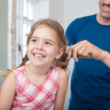 A father happily doing his daughters hair for her.