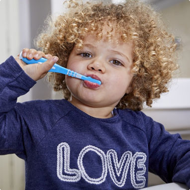 A young, curly haired boy brushing his teeth.