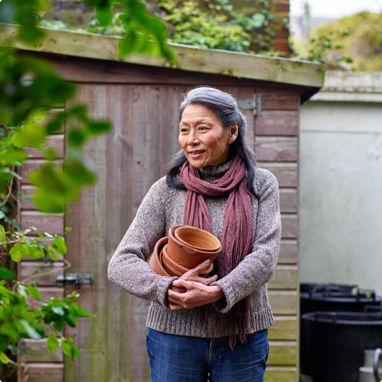 A late middle aged woman retrieving pots from her garden shed.