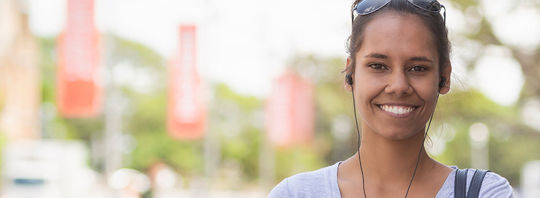 A young woman with her headphones in walking through the city.