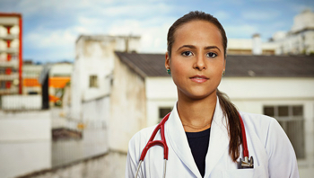 A female doctor with a stethoscope standing in an urban environment.